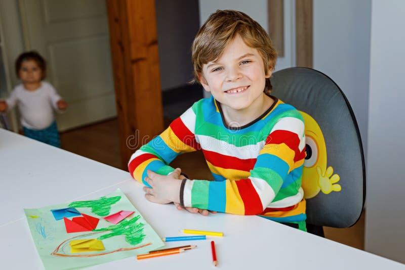 Der Kleinkindjunge, der Papierorigamitulpe macht, blüht für eine Postkarte für Mutter ` s Tag oder Geburtstag mit Kleinkind des k stockfotografie