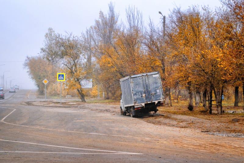 Der Kleinlaster ohne Rad auf einem Straßenrand im Herbst bewölkt stockbilder