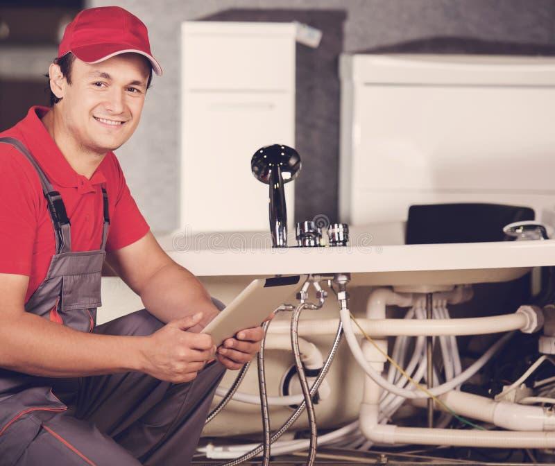 Der Klempner repariert die Rohre Männliche Spezialistenklempnerreparaturen lizenzfreies stockbild