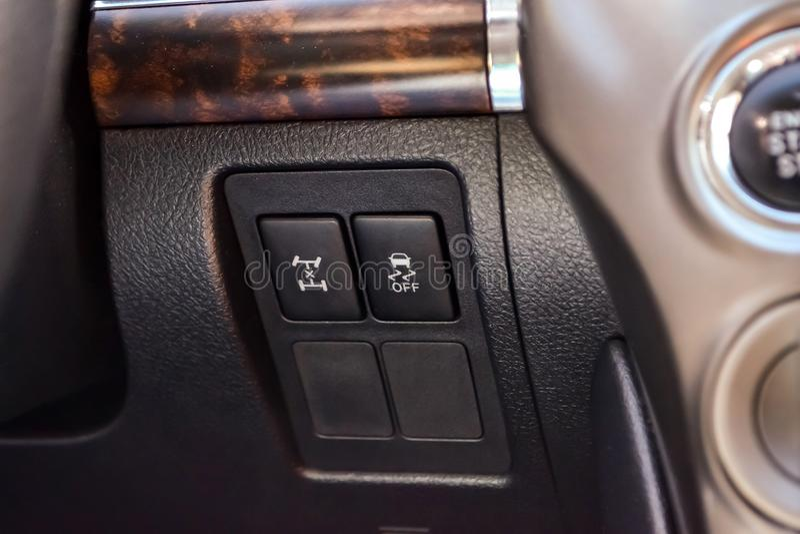 Der Knopf für das Stabilitätskontrollsystem und -blockierung des Mitteldifferentials auf schwarzer Platte des Autos nahe dem Lenk lizenzfreie stockfotografie