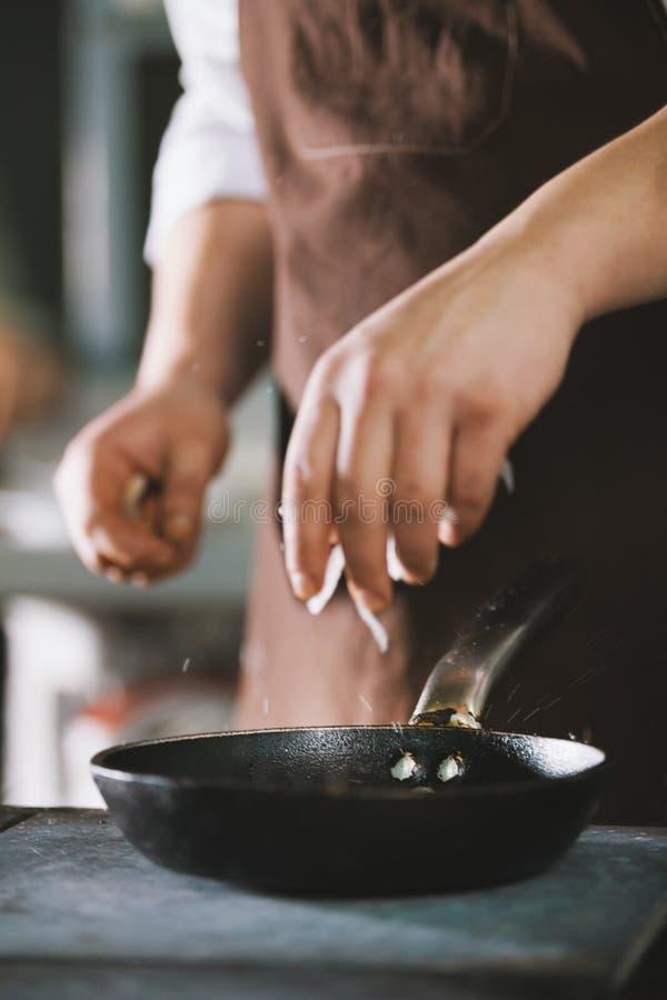 Der Koch fügt Gewürze und Zwiebel Lebensmittel hinzu stockbilder
