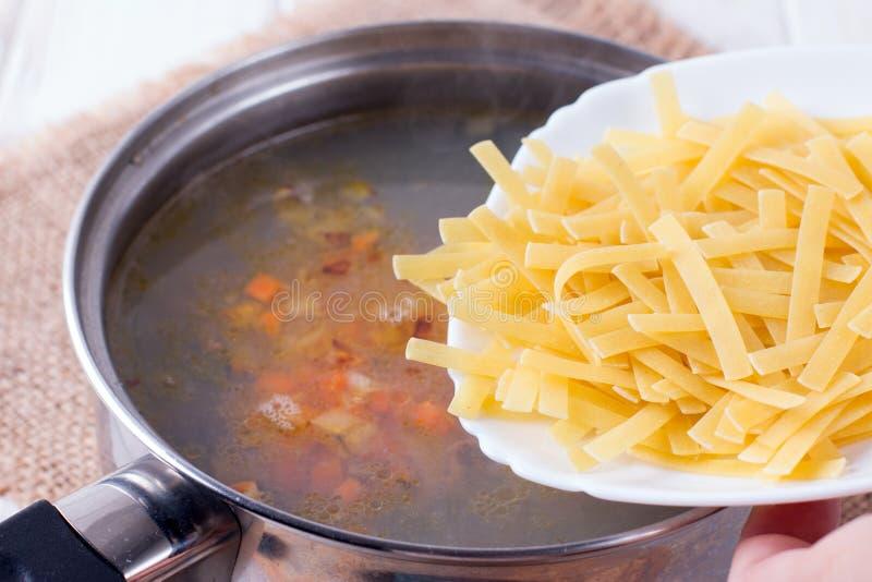 Der Koch fügt Makkaroni der Suppe hinzu lizenzfreie stockfotografie