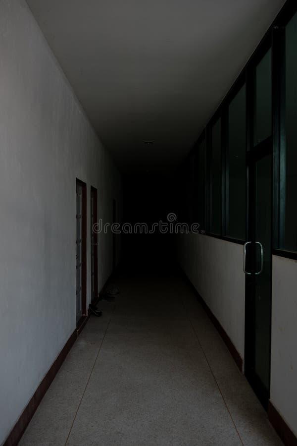 Der Korridor mit Dunkelheit, die dem Ende furchtsam betrachtet stockbilder