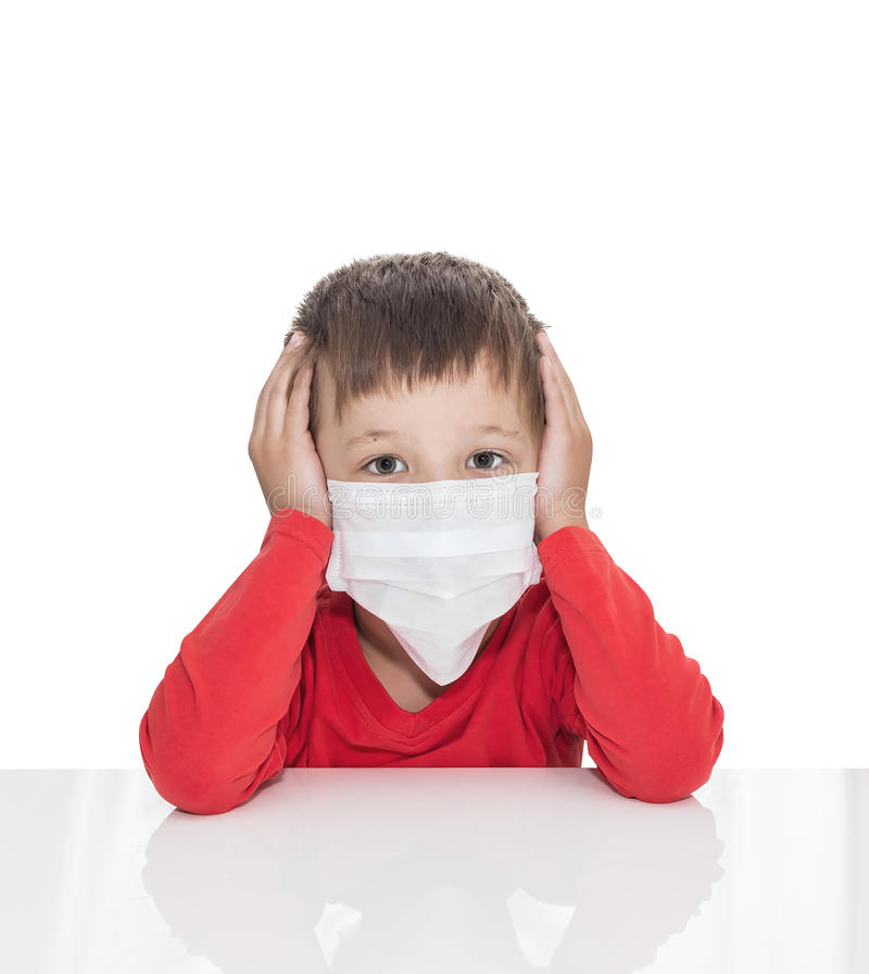 Der kranke fünfjährige Junge sitzt an einem weißen Tisch mit Medizingesundheitswesenmaske für ist Virus des Schutzes wieder lizenzfreie stockbilder