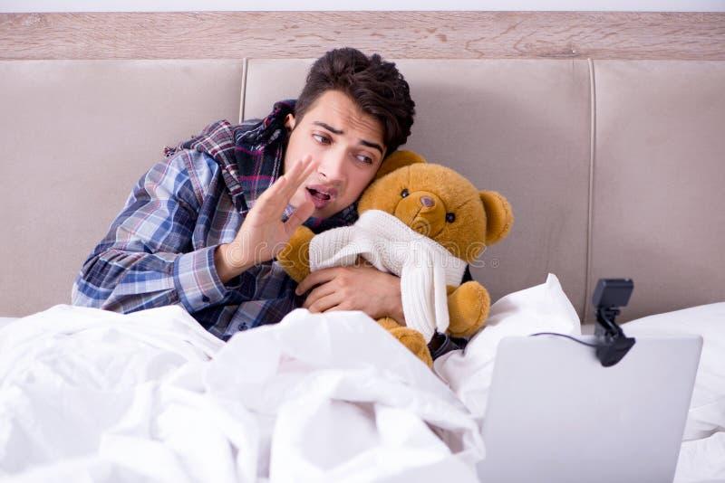 Der kranke Mann, der unter Grippe im Bett leidet lizenzfreies stockfoto