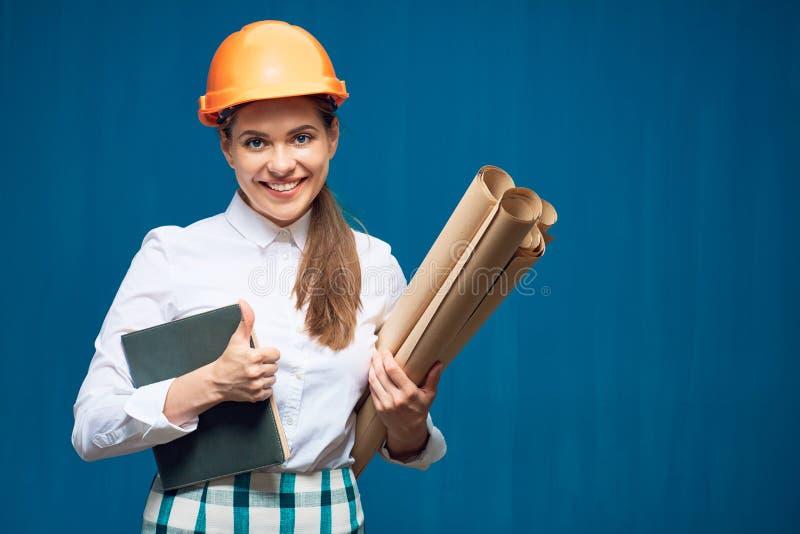 Der lächelnde Frauenarchitekt, der Buch halten und das Papier planen stockbild