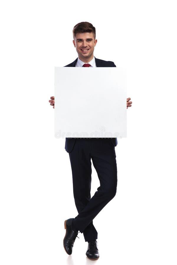 Der lächelnde Geschäftsmann, der mit den Beinen steht, kreuzte die weißen Griffe sich leeren lizenzfreies stockfoto