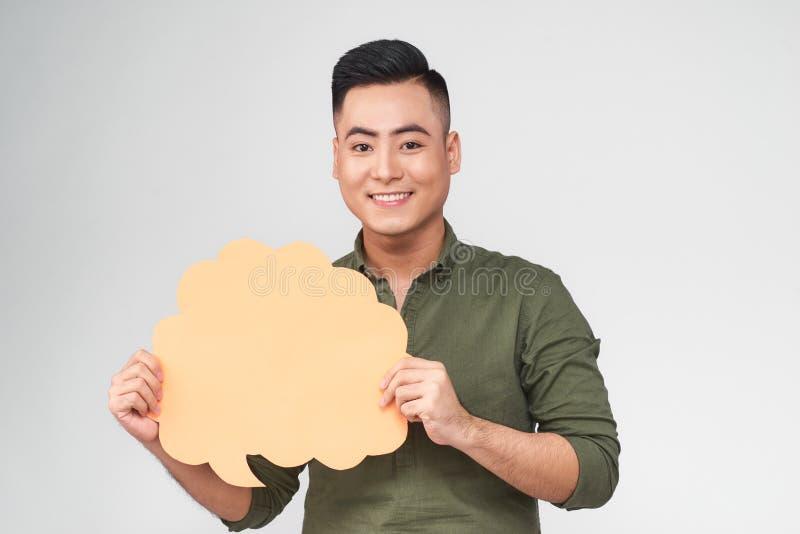 Der lächelnde junge asiatische Mann, der Rede hält, sprudeln auf grauem Hintergrund lizenzfreie stockfotografie