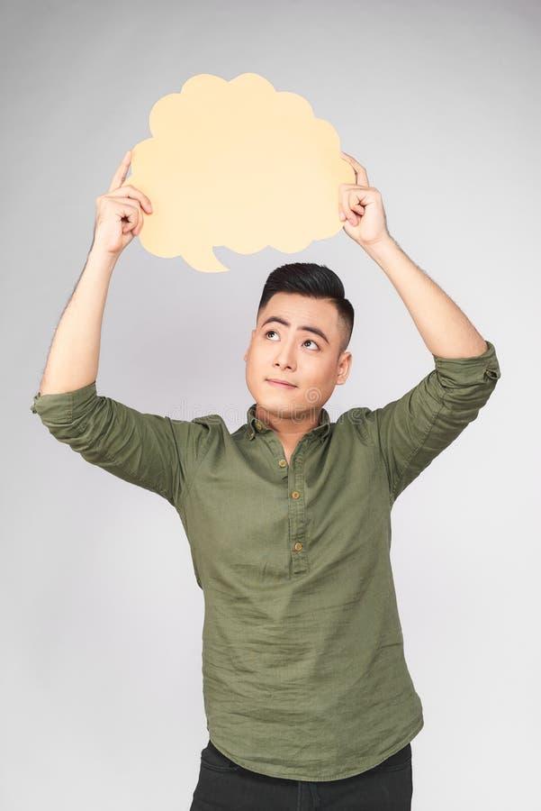 Der lächelnde junge asiatische Mann, der Rede hält, sprudeln auf grauem Hintergrund lizenzfreie stockfotos