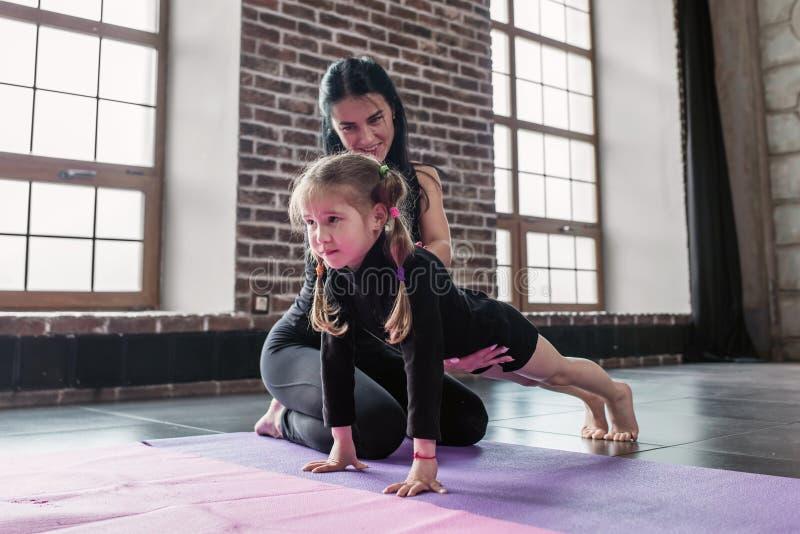 Der lächelnde Kinderturnhallentrainer, der mit einer Vertretung des kleinen Mädchens arbeitet, wie man Planke trainieren im Eignu stockfotografie