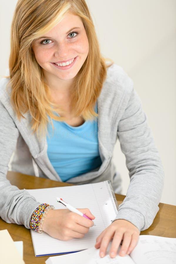 Der lächelnde Studentenjugendliche, der hinter Schreibtisch sitzt, schreiben stockbild