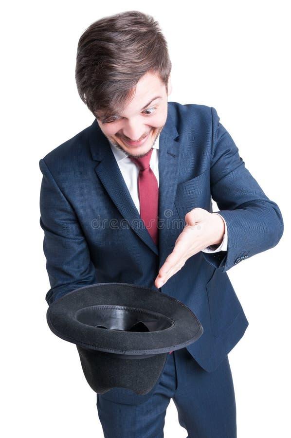Der lächelnde tragende Anzug des Mannes, der Hut hält, mögen bitten stockfoto