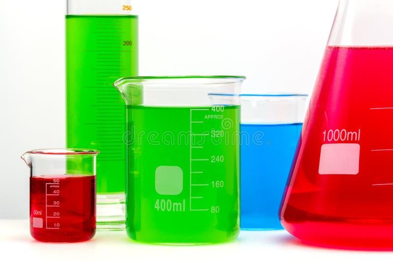 Der Laborglassatz, der mit bunten hellen Substanzen gefüllt wird, schließen oben lizenzfreie stockfotografie