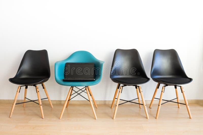 Der Laptop auf einem Stuhl Blauer Stuhl unter Schwarzem auf einem weißen Hintergrund stockbilder