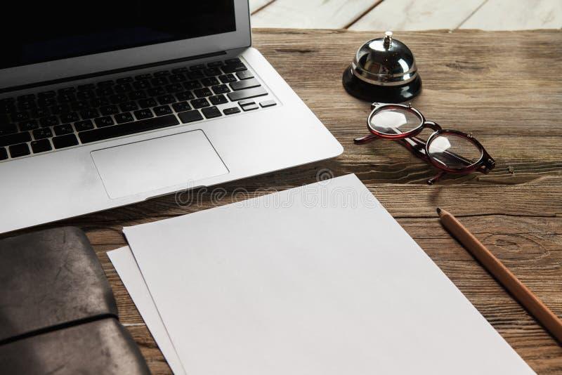 Der Laptop, das leere Papier, die Gläser und das Glöckchen an stockfotos