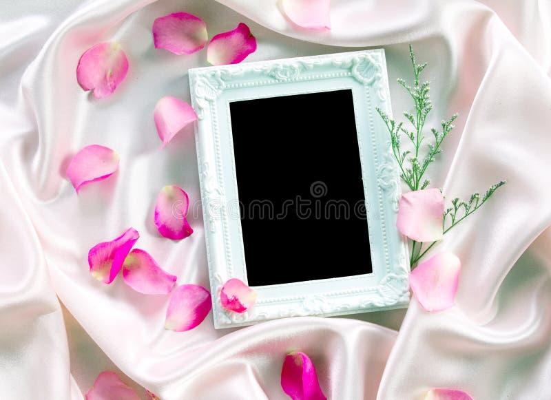 der leere Fotorahmen mit einem süßen rosa Rosenblumenblatt des Blumenstraußes an lizenzfreie stockfotos