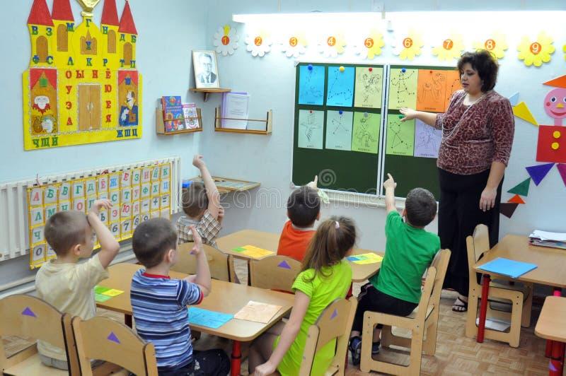 Der Lehrer beschäftigt die Kinder im Kindergarten lizenzfreie stockfotos