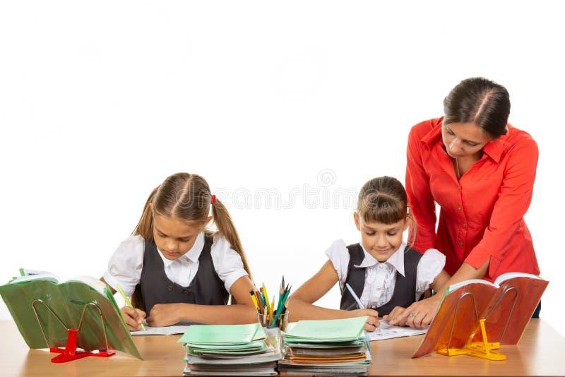 Der Lehrer geht um die Schüler, schaut in das Notizbuch, die Schüler lösen die Aufgabe lizenzfreies stockfoto