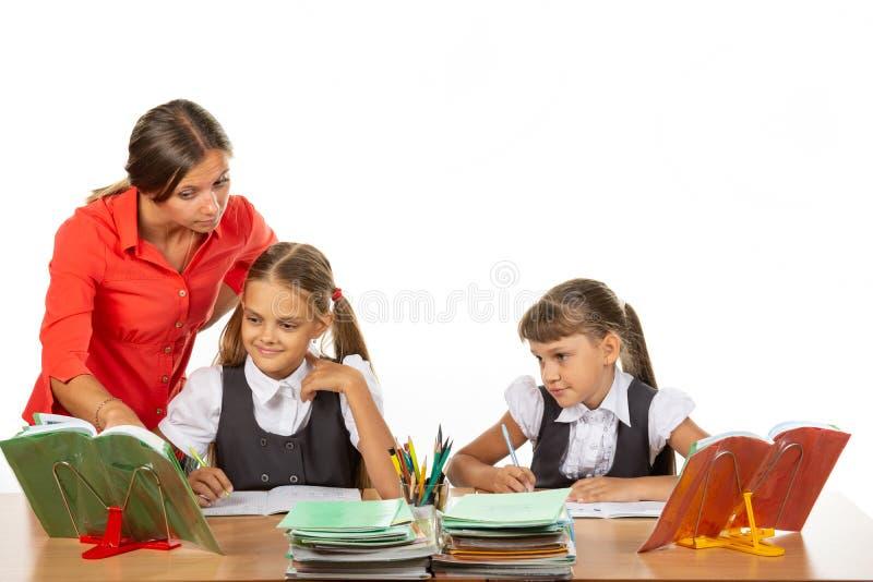 Der Lehrer hilft, die Aufgabe des Schülers zu verstehen stockfotos