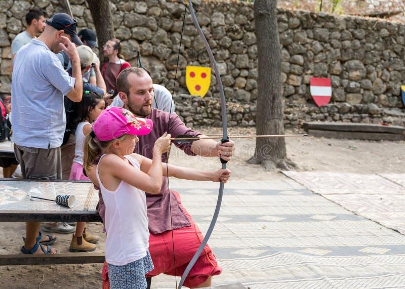 Der Lehrer unterrichtet das Besucherbogenschießen am Jahrbuchfestival ` Jerusalem-Ritter ` lizenzfreies stockbild