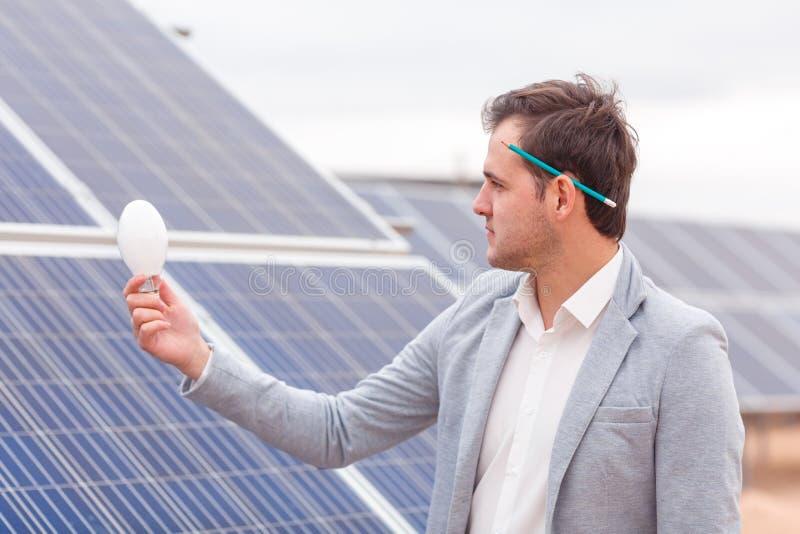 Der Leiter hält eine Glühlampe in seiner Hand vor dem hintergrund der Sonnenkollektoren lizenzfreie stockbilder