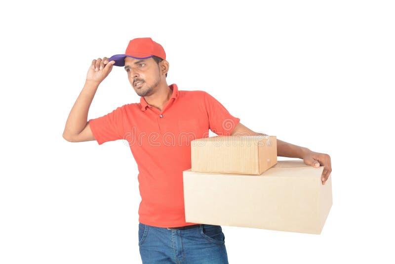 Der Lieferer, der Karton hält, packt Hand auf Kappe in der Uniform ein stockfoto