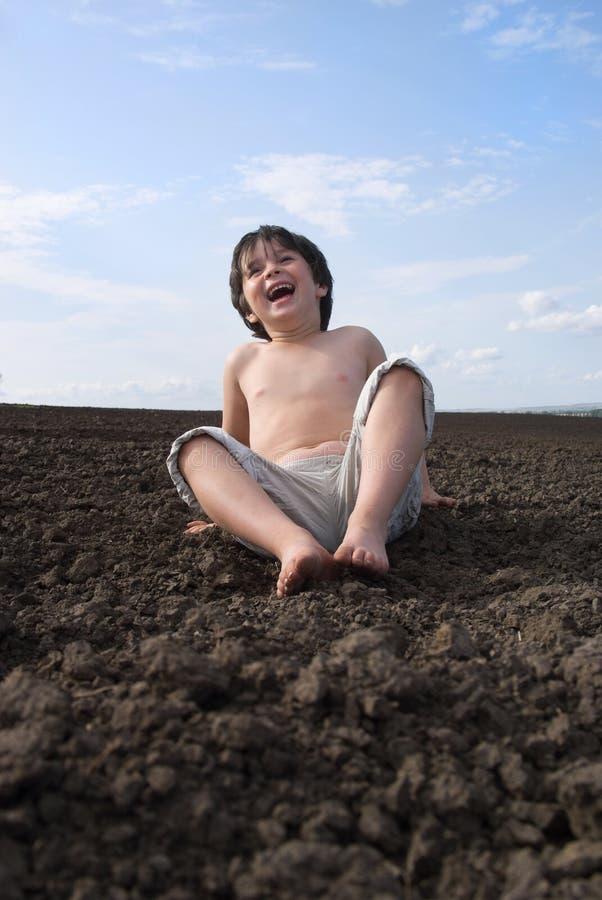 Der liitle Junge auf schwarzer Erde lizenzfreies stockbild