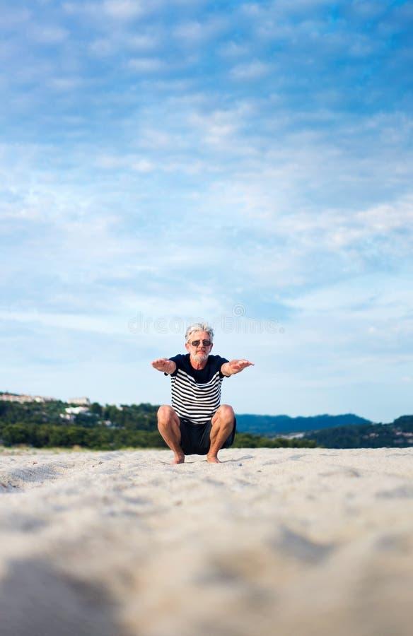 Der ?ltere Mann, der das Ausdehnen tut, trainiert auf dem Strand lizenzfreie stockbilder