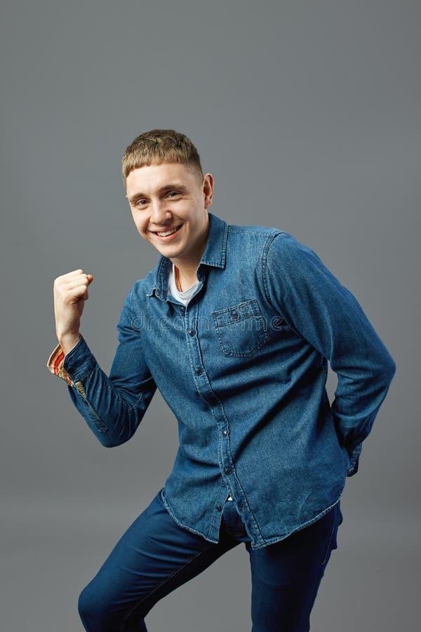 Der lustige Kerl, der in einem Jeanshemd gekleidet wird, zeigt seine Energie mit seiner Hand im Studio auf dem grauen Hintergrund stockfotos