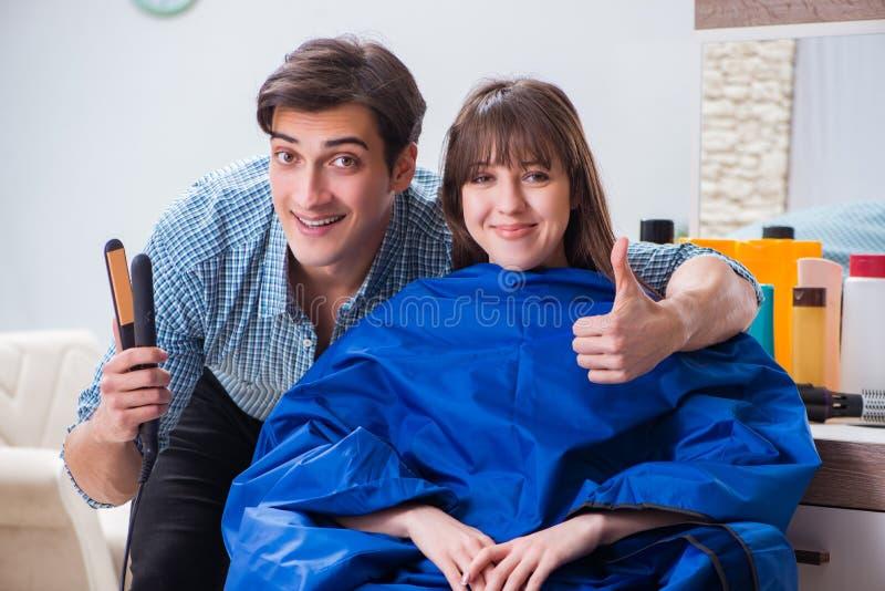 Der männliche Friseur des Mannes, der Haarschnitt für Frau tut stockbild