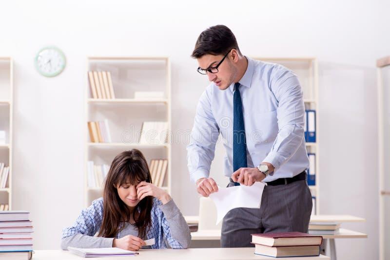 Der männliche Lektor, der der Studentin Vortrag gibt stockbilder