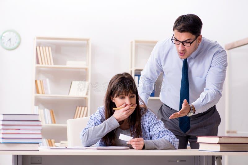 Der männliche Lektor, der der Studentin Vortrag gibt stockbild