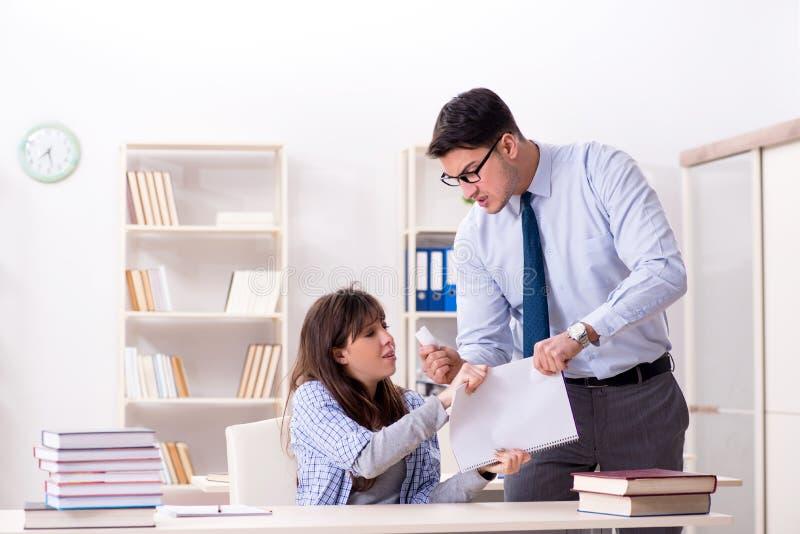 Der männliche Lektor, der der Studentin Vortrag gibt lizenzfreie stockbilder