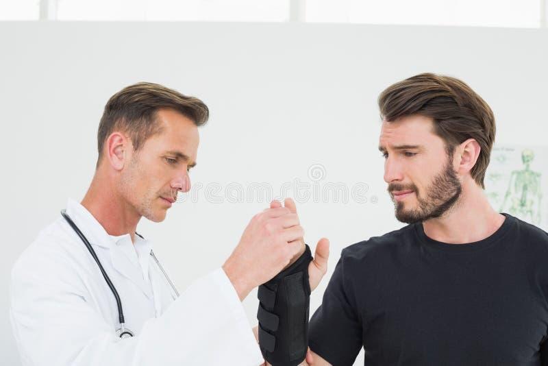 Der männliche Physiotherapeut, der a überprüft, bemannt Handgelenk stockfoto