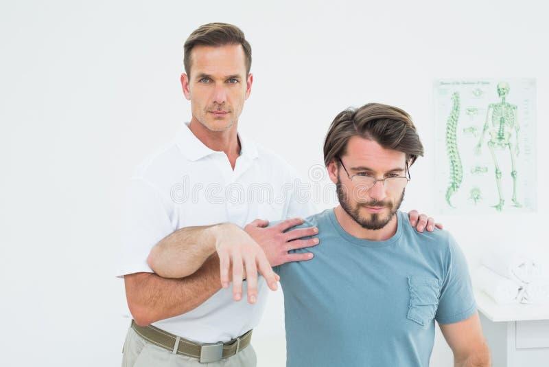 Der männliche Physiotherapeut, der ein junges ausdehnt, bemannt Arm stockfoto