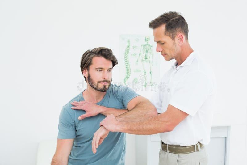 Der männliche Physiotherapeut, der ein junges ausdehnt, bemannt Hand stockbilder
