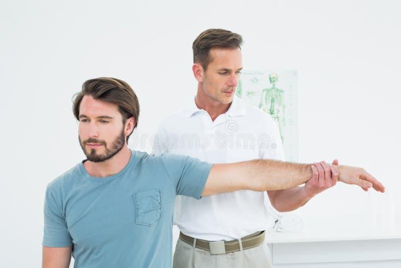 Der männliche Physiotherapeut, der ein junges ausdehnt, bemannt Hand lizenzfreies stockbild