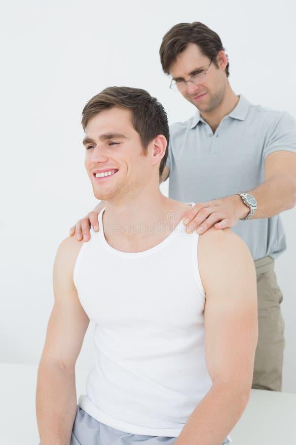 Der männliche Physiotherapeut, der ein junges massiert, bemannt Schulter lizenzfreies stockfoto