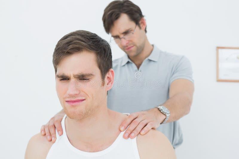 Der männliche Physiotherapeut, der ein junges massiert, bemannt Schulter lizenzfreie stockfotografie