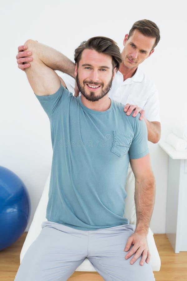 Der männliche Physiotherapeut, der ein Lächeln ausdehnt, bemannt Arm stockbild