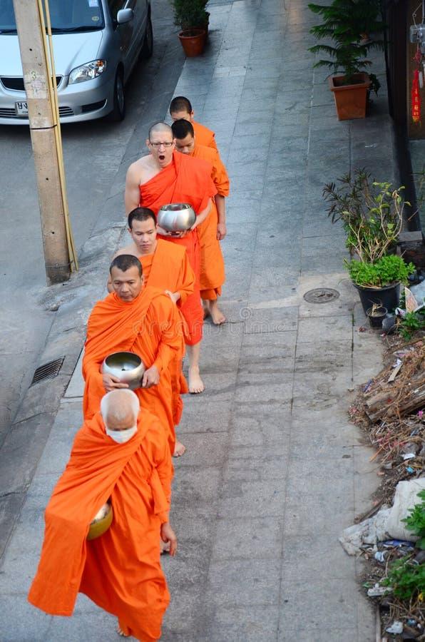 Der Mönch, der auf die Straße für Leute geht, beten und setzten Lebensmittelangebote stockbilder