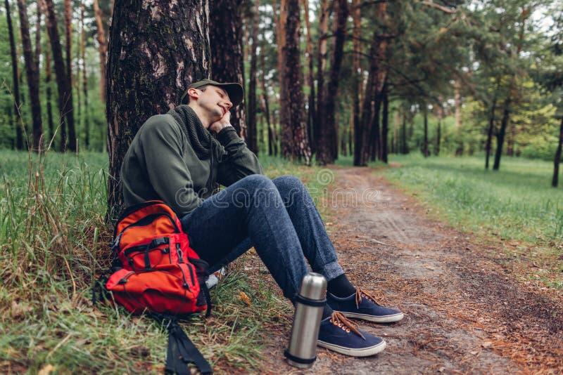 Der müde Manntourist, der im Frühjahr der Waldreisende schläft, stoppte, um Rest zu haben kampierend, Reisen und Sportkonzept stockfotos