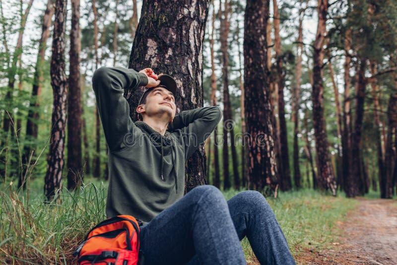 Der m?de Manntourist, der im Fr?hjahr der Waldreisende schl?ft, stoppte, um Rest zu haben kampierend, Reisen und Sportkonzept stockbild