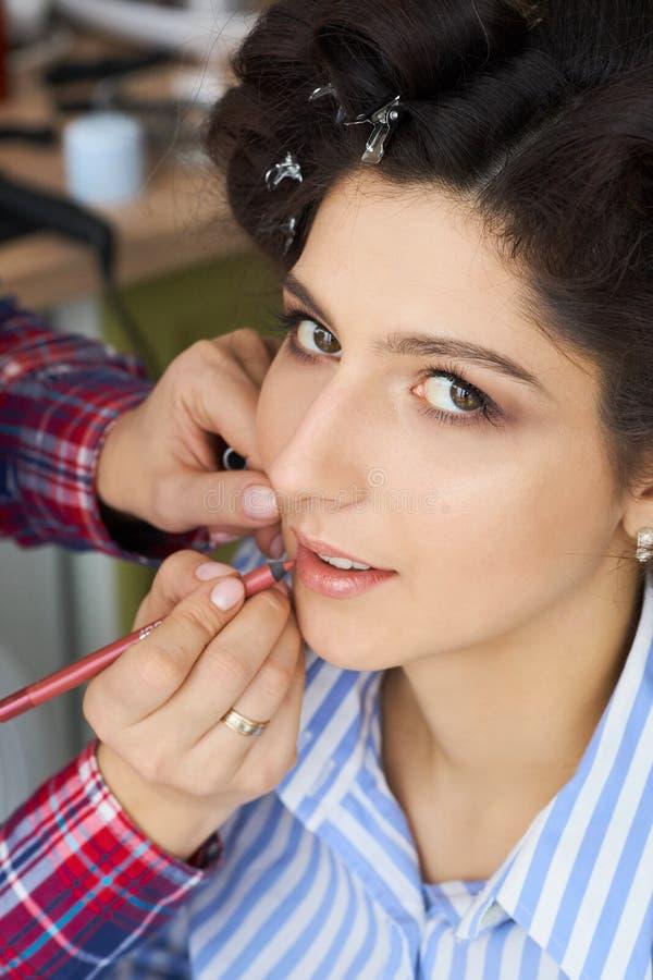 Der Make-upkünstler, der ein Make-up für Braut tut Maskenbildner wendet roten Lippenstift an Schönes Frauengesicht Hand des Makes lizenzfreies stockfoto