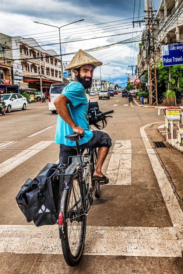 Der Mann, der auf das Fahrrad in Pakse, Laos reist lizenzfreie stockbilder