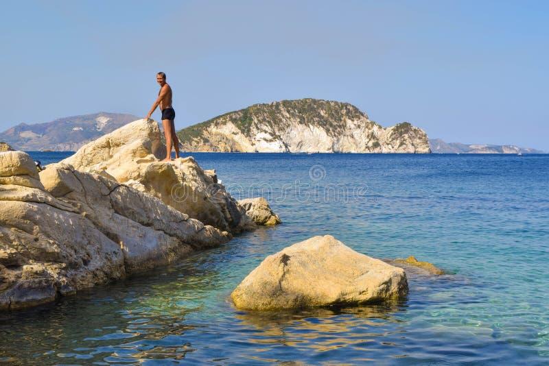 Der Mann auf dem Felsen stockfoto
