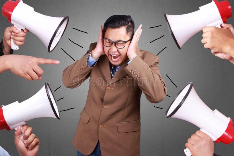 Der Mann bedeckte sein Ohr Geräusche ignorierend stockfotos