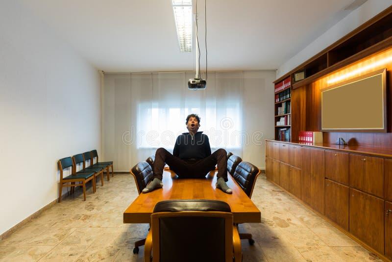 Der Mann in den Gesten der Verrücktheit im Konferenzzimmer stockfoto