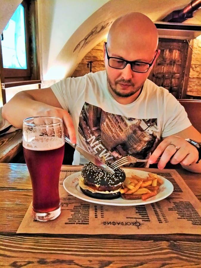 Der Mann in den Gläsern einen Hamburger essend und ein Bier an der Bar trinkend lizenzfreies stockfoto