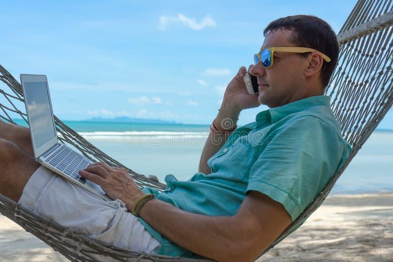 Der Mann in den Tropen und mit den Computer Jungen die Schönheit, die in einer Hängematte mit dem Laptop im tropischen liegt stockfotografie